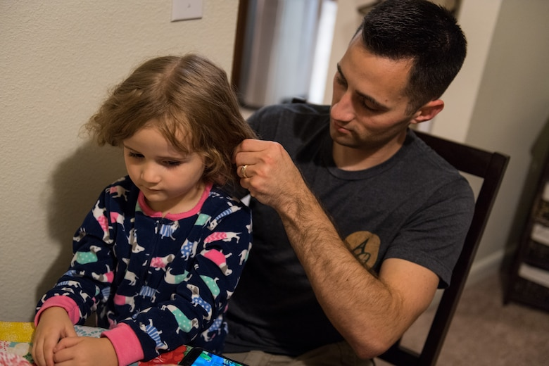 Airman 1st Class Joshua Bruner, 26th Operational Weather Squadron weather forecaster, helps his daughter, Juliana, with her hair at Barksdale Air Force Base, La., Oct 19, 2019. (U.S. Air Force photo by Airman 1st Class Lillian Miller)