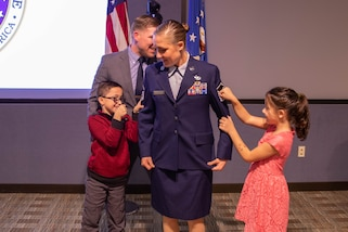 U.S. Air Force Master Sgt. Christina Anders has her rank pinned on by her son, daughter and Aaron Plichta, a member of Joint Task Force Civil Support. Senior Master Sgt. Matthew Larsen, who served with Anders at the 821st Contingency Response Squadron at Travis Air Force Base, Ca., presided over the ceremony and administered the senior non-commissioned officer charges. (Official DoD photo by Mass Communication Specialist 3rd Class Michael Redd/RELEASED)