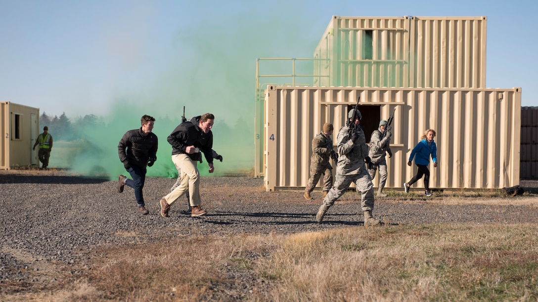 92nd Security Forces Squadron Airmen evacuate local media members to a safe area after a simulated explosion training exercise during a Year of the Defender media day event at Fairchild Air Force Base, Washington, Oct. 29, 2019. Security forces Airmen are charged with training and maintaining combat readiness on weapons and protective gear for all Airmen, ensuring everyone is deployment ready. (U.S. Air Force photo by Senior Airman Ryan Lackey)
