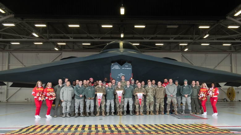 National Football League's Kansas City Chiefs linemen and cheerleaders pose for a photo in front of a B-2 Spirit with members of Team Whiteman.