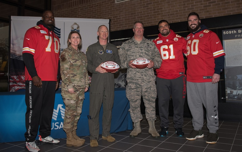 National Football League's Kansas City Chiefs present game balls to U.S. Air Force Col. Seth Graham, the 509th Bomb Wing vice commander, and Lt. Col. Chard Larson, the 131st Aircraft Maintenance Squadron commander, during a visit to Whiteman Air Force Base, Missouri, Oct. 29, 2019.
