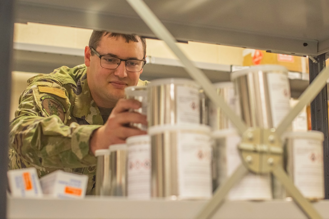 Staff Sergeant Nicholas Tendam, 100th Logistics Readiness Squadron assistant noncommissioned officer in charge of hazmart, stacks cans of corrosion prevention fluid Oct. 28, 2019, at RAF Mildenhall, England. Materials are separately stored at the hazmart pharmacy according to the hazard they present. (U.S. Air Force photo by Airman 1st Class Joseph Barron)