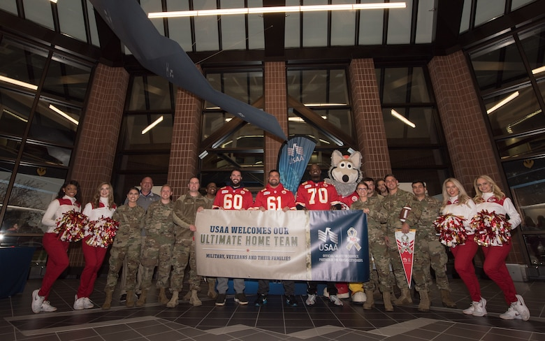 "National Football League's Kansas City Chiefs linemen and cheerleaders, members of Team Whiteman and USAA representatives pose for a photo with a Salute to Service banner that reads, ""USAA Welcomes Our Ultimate Home Team. Military, Veterans and their Families."""