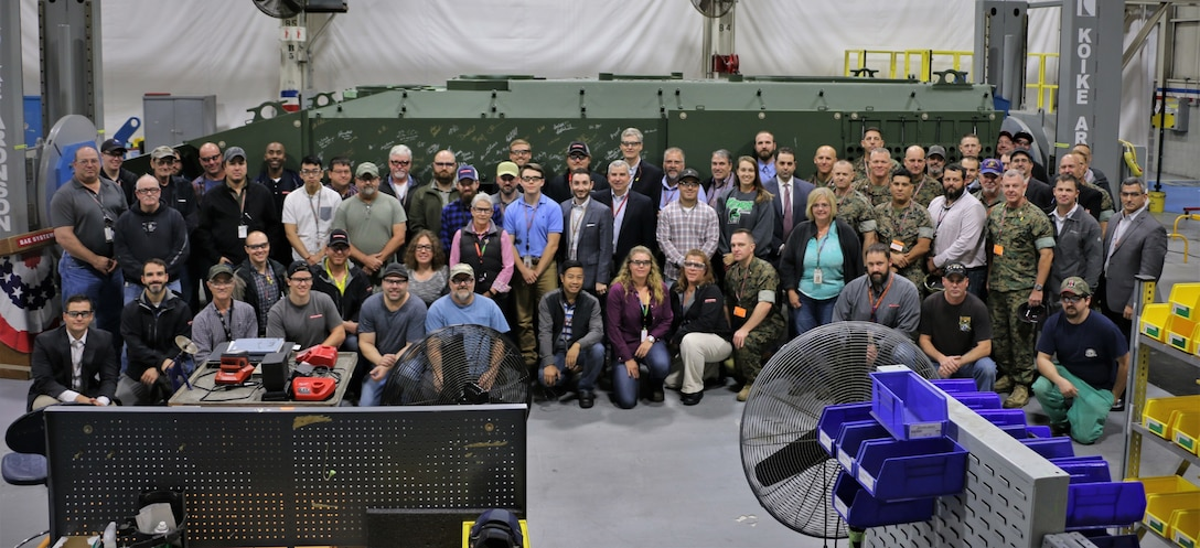 Representatives from Program Manager Advanced Amphibious Assault at Program Executive Officer Land Systems, Marine Corps Combat Development Command, Combat Development and Integration and 3rd Assault Amphibian Battalion pose in front of an unfinished Amphibious Combat Vehicle with the manufacturing workforce in York, Pennsylvania, on Oct. 16, 2019.