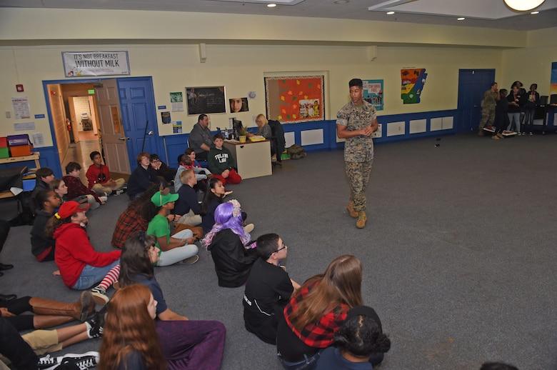 A Marine briefs children at a school assembly