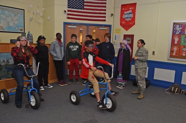 Children ride a tricycle with alcohol simulation goggles on