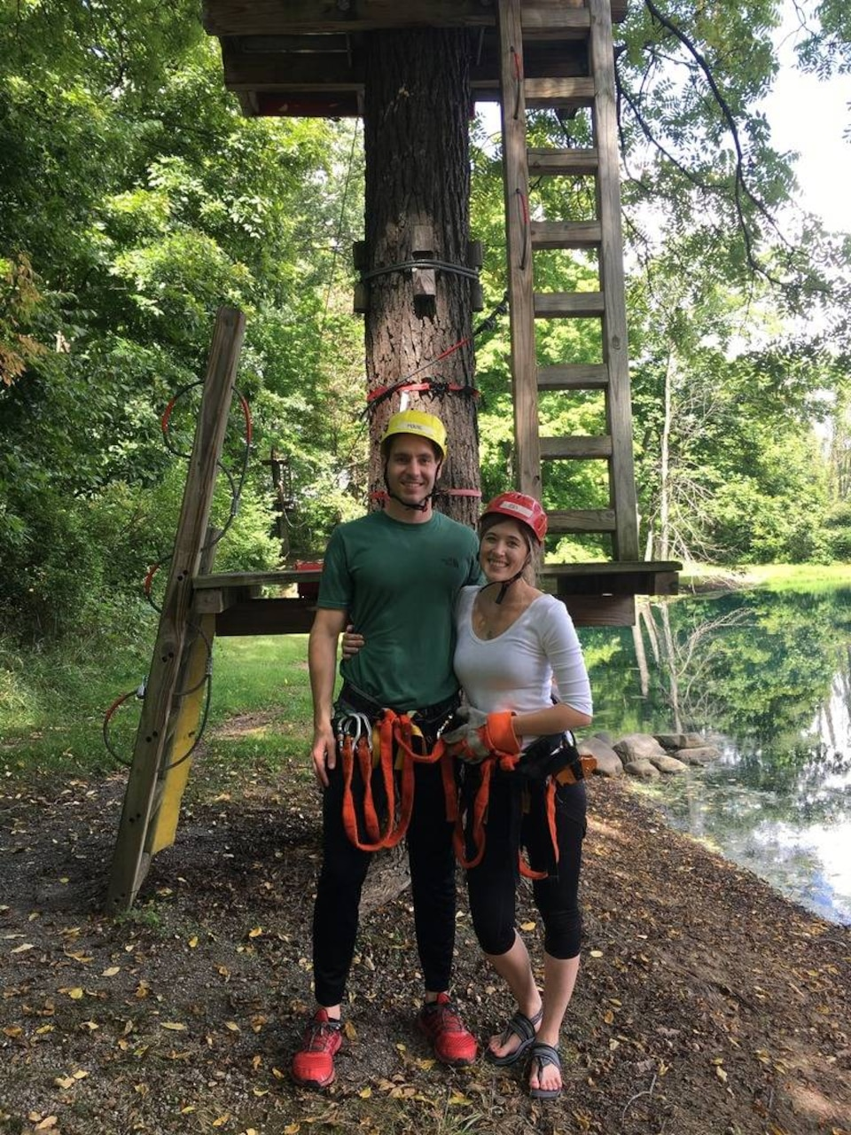 A man and woman wearing helmets stand outdoors in front of a tree. The tree has wooden platforms and ladders attached to its trunk.