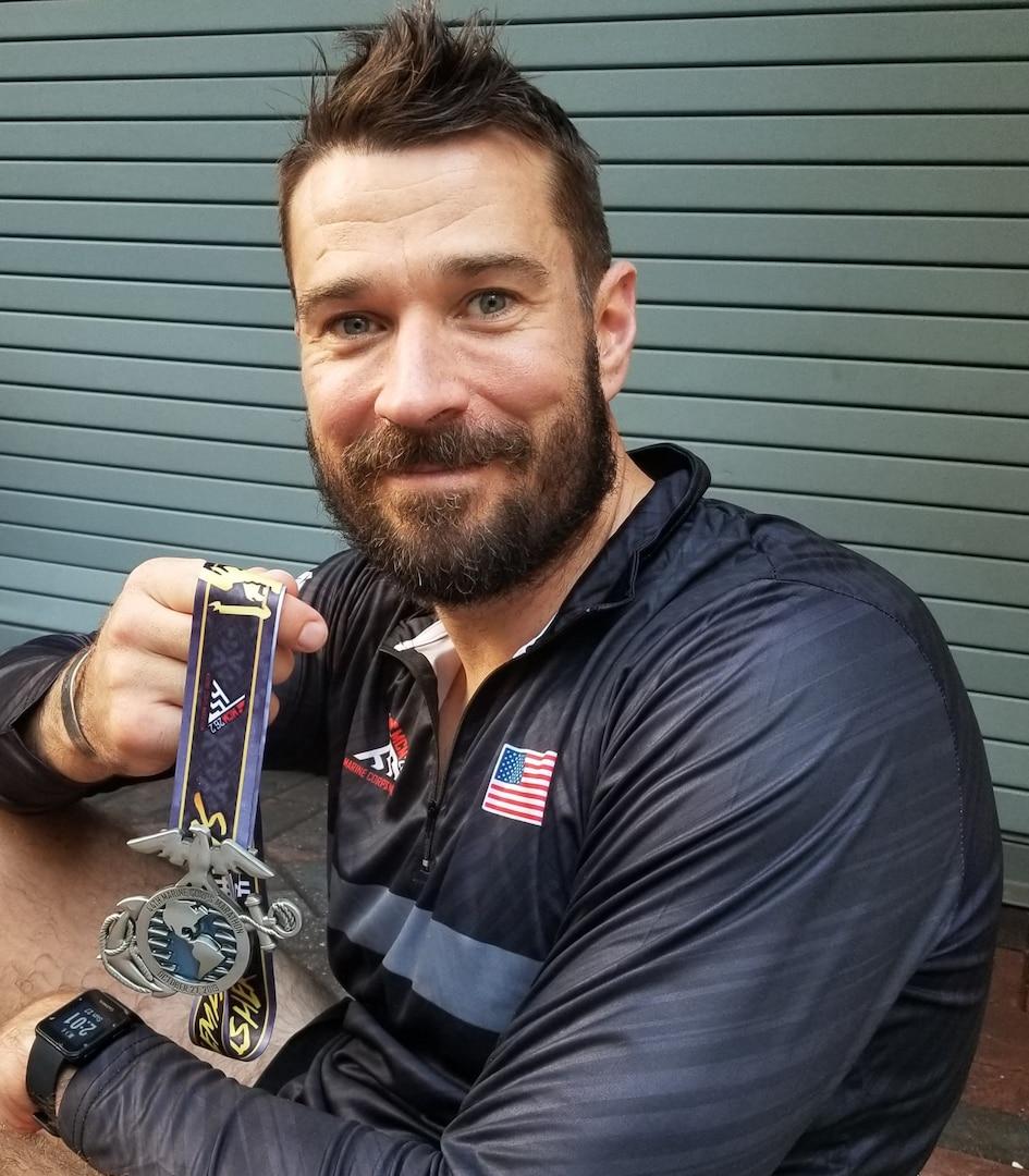 Runner posing with finisher's medal