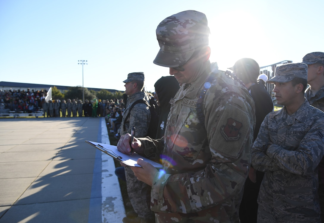U.S. Air Force Master Sgt. David Gustafson, 334th Training Squadron flight chief, judges a performance during the 81st Training Group drill down on the Levitow Training Support Facility drill pad at Keesler Air Force Base, Mississippi, Nov. 1, 2019. Airmen from the 81st TRG competed in a quarterly open ranks inspection, regulation drill routine and freestyle drill routine. Keesler trains more than 30,000 students each year. While in training, Airmen are given the opportunity to volunteer to learn and execute drill down routines. (U.S. Air Force photo by Kemberly Groue)