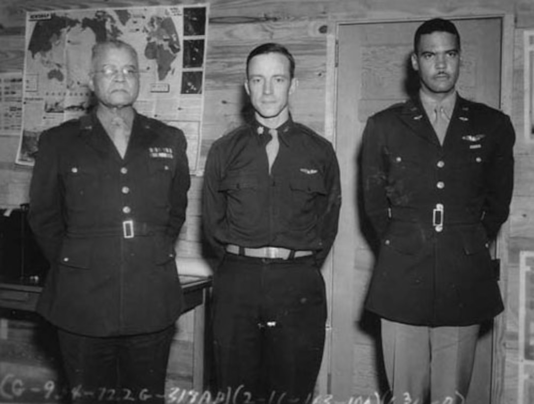 Three men in military uniforms stand for a photo.