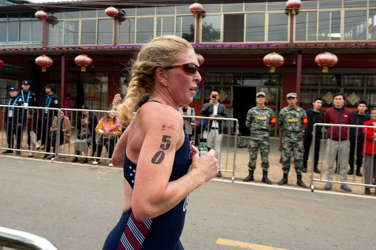 "Woman triathlon athlete runs with ""50"" on her right arm."