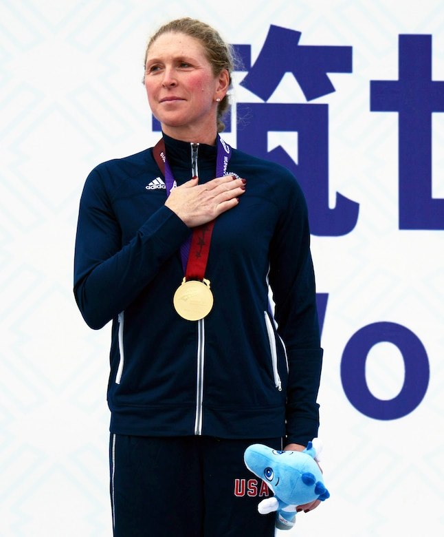 Woman wearing a blue track suit and a gold medal holds a stuffed animal in her left hand and holds her right hand over her heart.