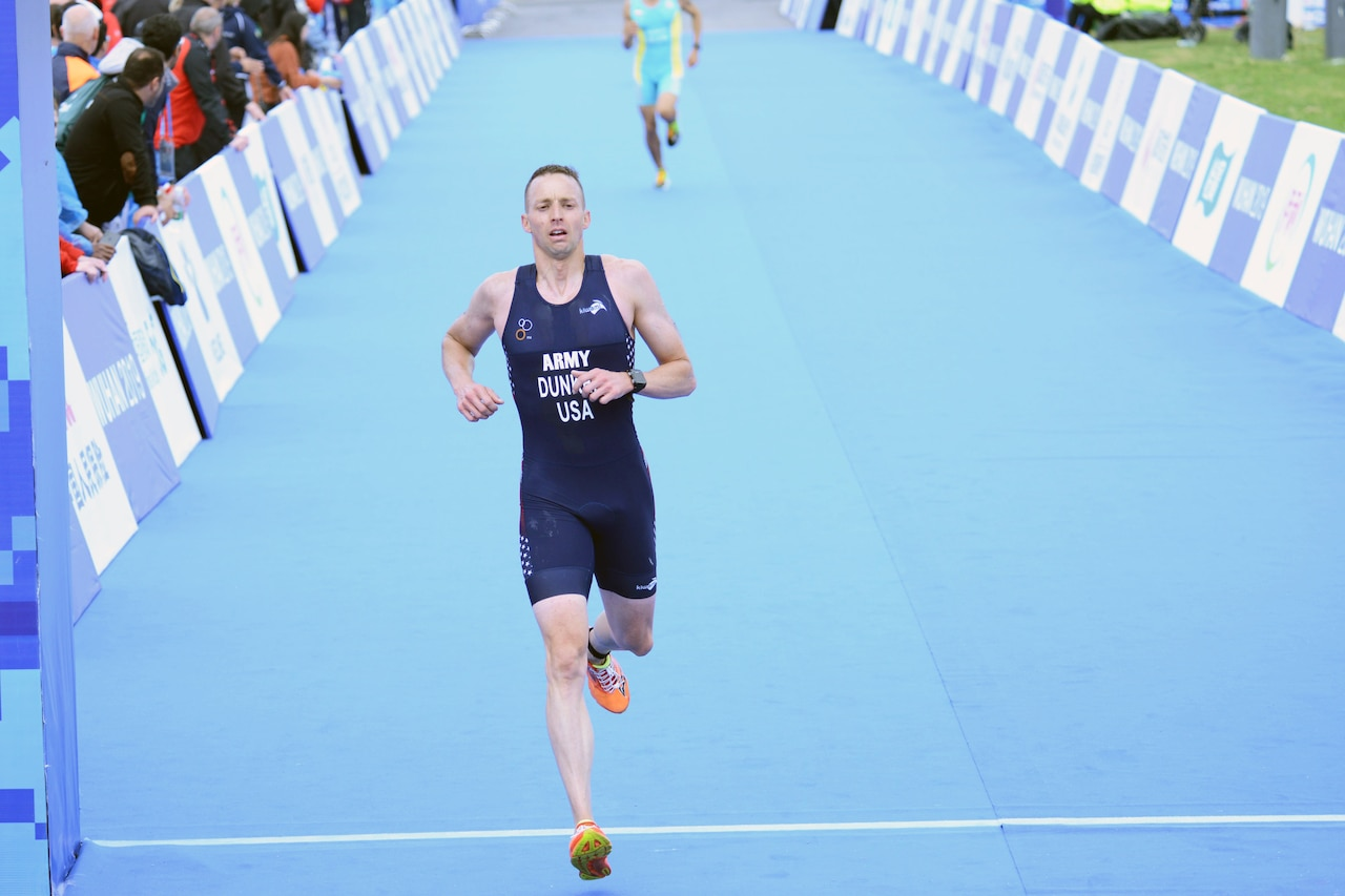 Male triathlete crosses the finish line for the running portion of the event.