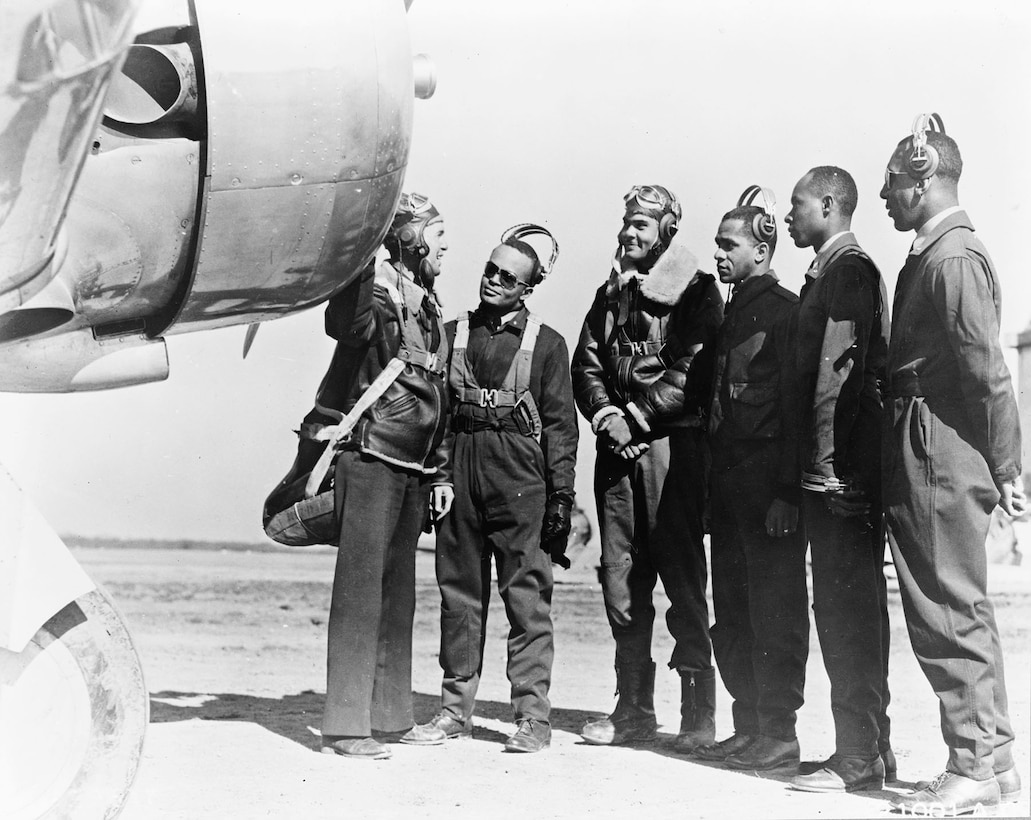 A group of airmen examines an aircraft propeller while an instructor points.