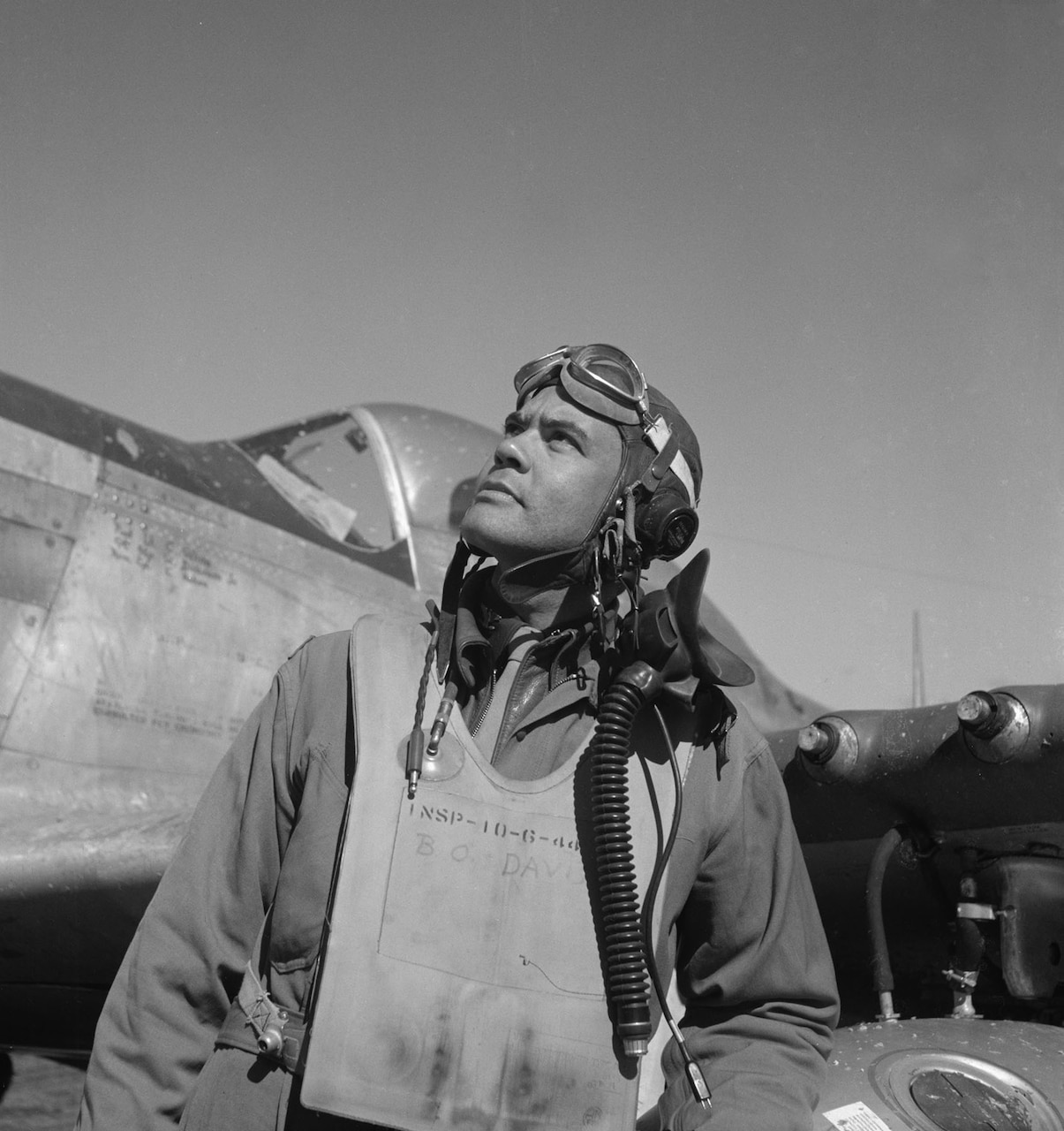 An airman looks at the sky while standing in front of a World War II-era aircraft.