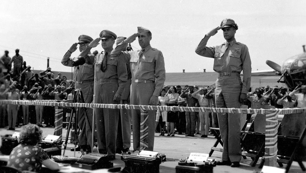 A group of service members salutes while standing on an elevated platform.