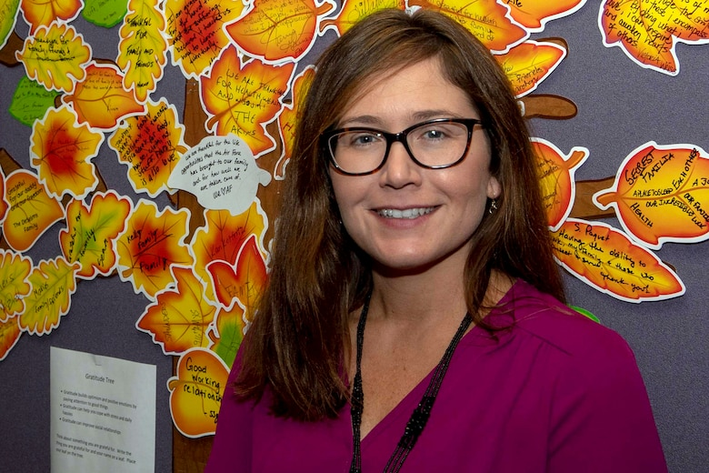 Jennifer S. Price, 916th Air Refueling Wing director of psychological health, poses for a photo in front of her Gratitude Tree.