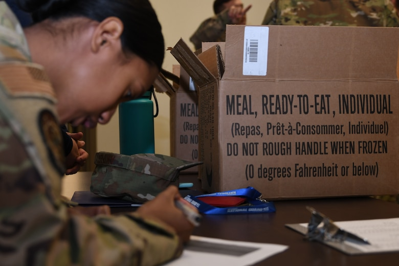 Senior Airman Angel Akino, 355th Force Support Squadron fitness apprentice, issues out Meals Ready to Eat at the end of the personnel deployment function line for Exercise Bushwhacker 19-08 at Davis-Monthan Air Force Base, Arizona, Cct. 31, 2019. The personnel deployment function line is a streamlined process that helps Airmen rapidly deploy in support of the Dynamic Wing. (U.S. Air Force photo by Airman 1st Class Blake Gonzales)