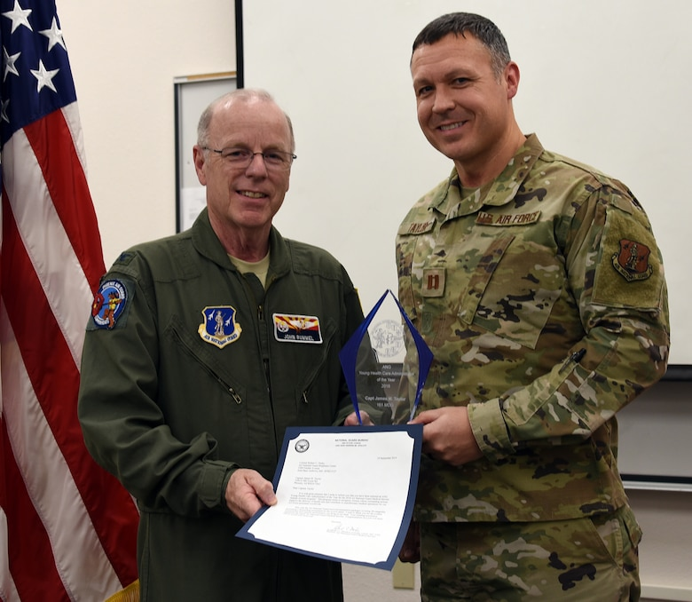 Col. John Rummel, 161st MDG commander presents Capt. James Taylor, 161st MDG medical readiness officer, the ANG Young Health Care Administrator of the year award at Goldwater Air National Guard Base, Phoenix, Nov. 2, 2019. (U.S. Air National Guard photo by Tech. Sgt. Michael Matkin)