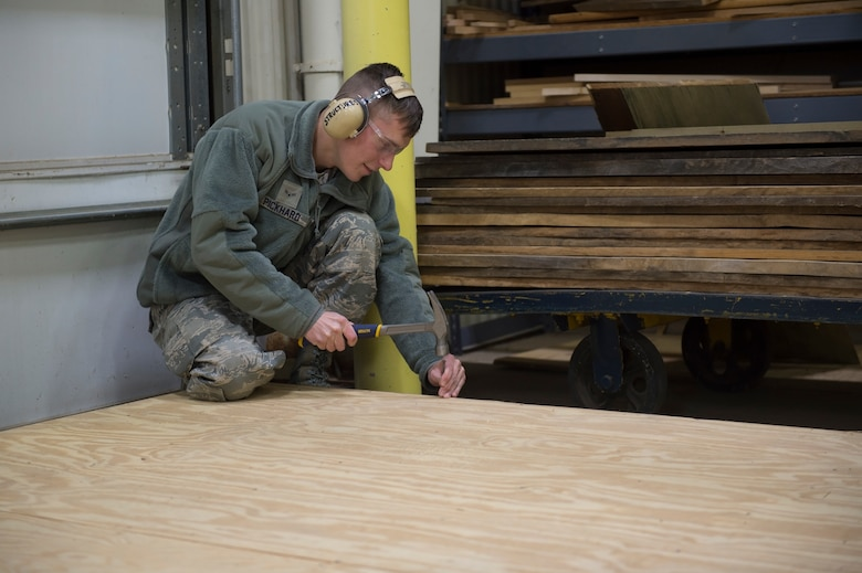 Airman 1st Class Austin Pickhard, 434th Civil Engineering Squadron structural helper, puts the finishing touches on the floor of a doll house Grissom Air Reserve Base, Indiana Nov. 3, 2019. The doll house is one of many bivouac operations that are used for training and exercise purposes here. (U.S. Air Force photo/Tech. Sgt. Jami K. Lancette)