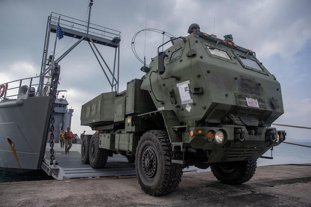 U.S. Marines with 12th Marine Regiment, 3rd Marine Division, and U.S. Soldiers with 97th Transportation Company, 10th Support Group, work together to quickly embark transportation vehicles and a High Mobility Artillery Rocket System on the U.S. Army Vessel Harpers Ferry (LCU-2022) during a joint service HIMARS embarkation training exercise in Kin, Okinawa, Japan, Oct. 31, 2019. This event marks the first time a Marine HIMARS was loaded on to an Army landing craft in the Indo-Pacific. Strategic mobility is key in the Indo-Pacific and the ability to transport the HIMARS over water is a vital capability that the 3rd Marine Division is now able to expand upon by partnering with the 10th Support Group. (U.S. Marine Corps photo by Lance Cpl. D'Angelo Yanez)