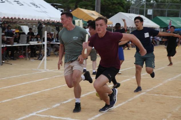 4X200メートルリレーで力走する海兵隊員。沖縄県名護市辺野古区で11月3日(日)、第46回辺野古区民運動会が区民運動場で開催され、米海兵隊基地キャンプ・シュワブと沖縄防衛局も招待され、参加しました。