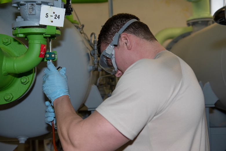 U.S. Air Force Senior Airman Joshua Skroch, 52nd Logistics Readiness Squadron petroleum, oil, and lubricants journeyman, connects a tube used to collect fuel samples to a fuel tank at Spangdahlem Air Base, Germany, Oct. 29, 2019. Skroch connected the tube to the tank and began collecting fuel samples for further testing in a lab. (U.S. Air Force photo by Airman 1st Class Alison Stewart)
