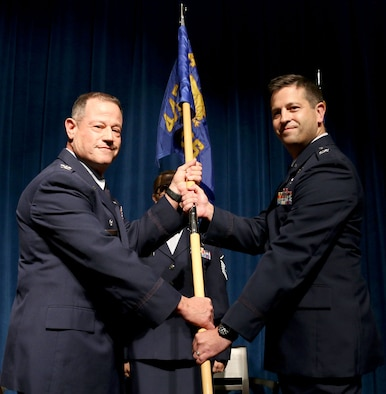 (left) 445th Airlift Wing Commander Col. Adam Willis, passes the guidon to Col. Hans Otto, incoming 445th Aerospace Medicine Squadron commander, during an assumption of command ceremony Oct. 6, 2019 held at the 88th Air Base Wing Medical Group.