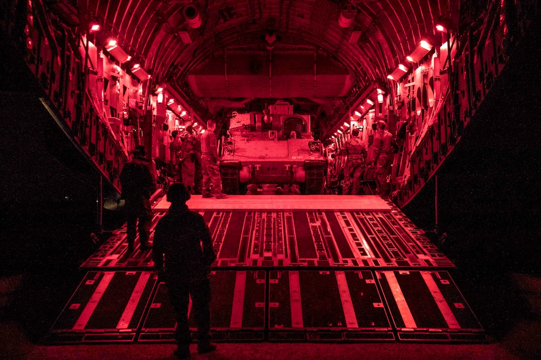 A military vehicle sits in an open aircraft, illuminated in red, as soldiers work inside it.