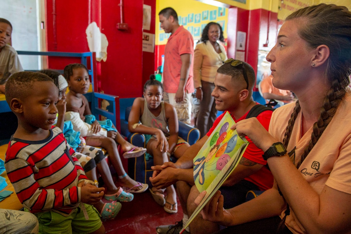 Two sailors read to a group of children in a red-painted room.