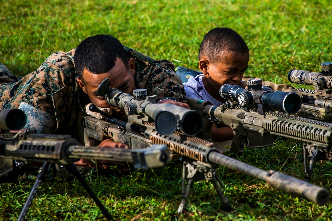 A U.S. Marine with 2nd Battalion, 3rd Marine Regiment, sights in on a sniper rifle with his son during the unit's Island Warrior Spouse and Family Day on Marine Corps Base Hawaii, Oct. 29, 2019. The event gave Marines and Sailors the opportunity to create a positive community and give something back to the families that support the unit.
