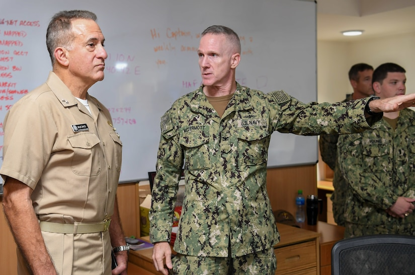 Capt. Charles McDermott, center, gives a tour of the Naval Coordination and Guidance for Shipping (NCAGS) facilities to Rear Adm. Jack Buono, the Superintendent of the U.S. Merchant Marine Academy. The U.S. Naval Forces Central Command NCAGS team has recently amplified their support to the region in support of Operation Sentinel, a multinational maritime security effort designed to increase surveillance of key waterways in the Middle East to ensure freedom of navigation. (U.S. Navy photo by Mass Communication Specialist 3rd Class Dawson Roth/Released)