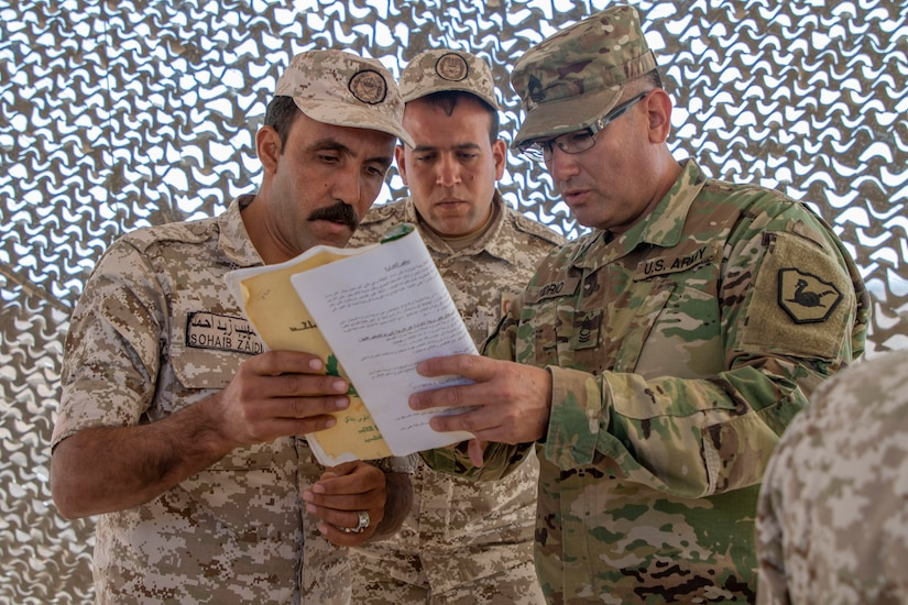 A U.S. Army Soldier, with Military Engagement Team-Jordan, 158th Maneuver Enhancement Brigade, Arizona Army National Guard, discusses a mathematical equation with Jordan Armed Forces-Arab Army (JAF) Soldiers during a Sniper Subject Matter Expert Exchange at a base outside of Amman, Jordan in October 2019. The United States is committed to the security of Jordan and to partnering closely with the JAF to meet common security challenges. (U.S. Army photo by Sgt. 1st Class Shaiyla B. Hakeem)