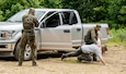 Members of the Polish Territorial Defense Forces receive training in checkpoint vehicle clearing techniques from members of West Virginia Army National Guard (WVARNG) Special Forces during Ridge Runner 19-02, June 24, 2019, in West Virginia. Ridge Runner is a WVARNG training program that provides various National Guard, active duty, and North Atlantic Treaty Organization (NATO) ally nation armed forces with training in irregular and asymmetrical warfare tactics and operations. (U.S. Army National Guard photo illustration by Edwin Wriston.) (This photo has been altered for security purposes by blurring out faces.)