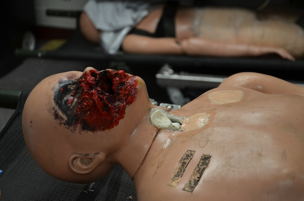 Ground charcoal is added to the red paint on the face of the manikin to create a realistic facial wound.  Moulage transforms low-fidelity manikins into combat casualties to simulate battlefield wounds or injuries to train combat medics.