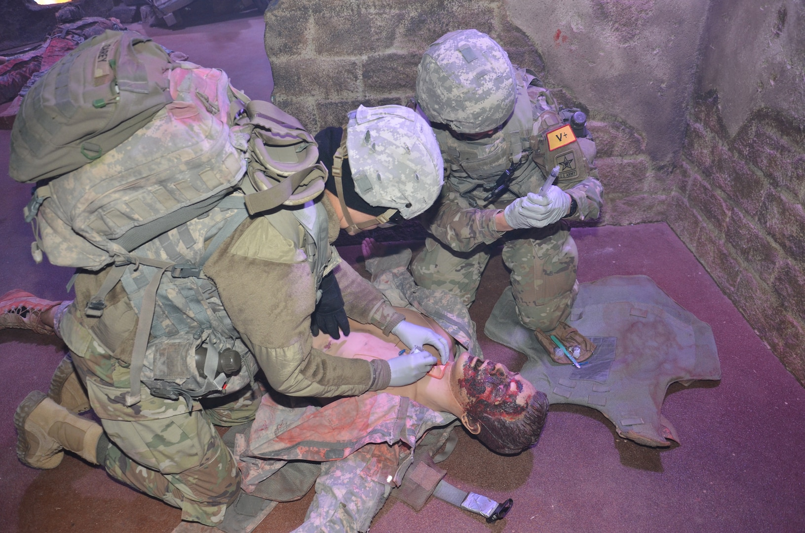 """Combat Medic Training program students at the Medical Education and Training Campus at Joint Base San Antonio-Fort Sam Houston conduct an emergency cricothyrotomy on a """"casualty"""" during simulation training. The """"wounded"""" manikin also presents with facial burns that were created with moulage techniques."""