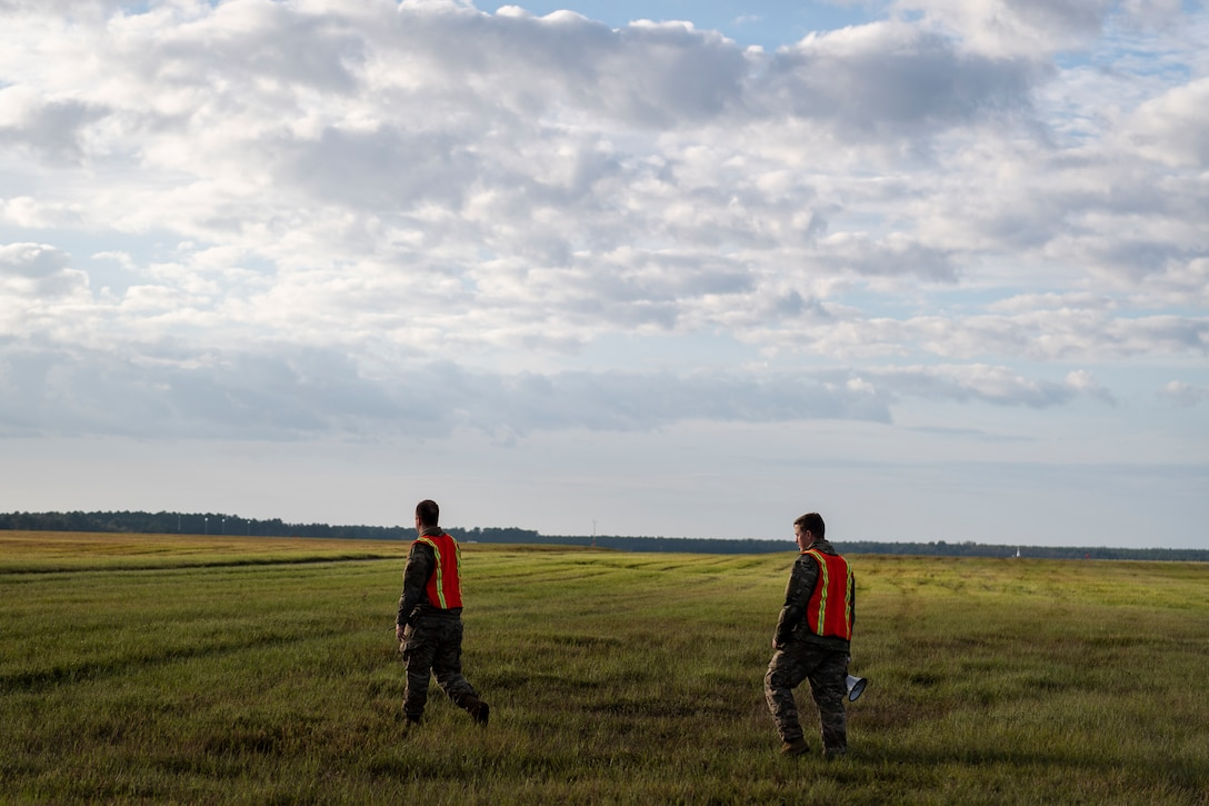 A photo of Airmen leading a foreign object debris walk across the airfield