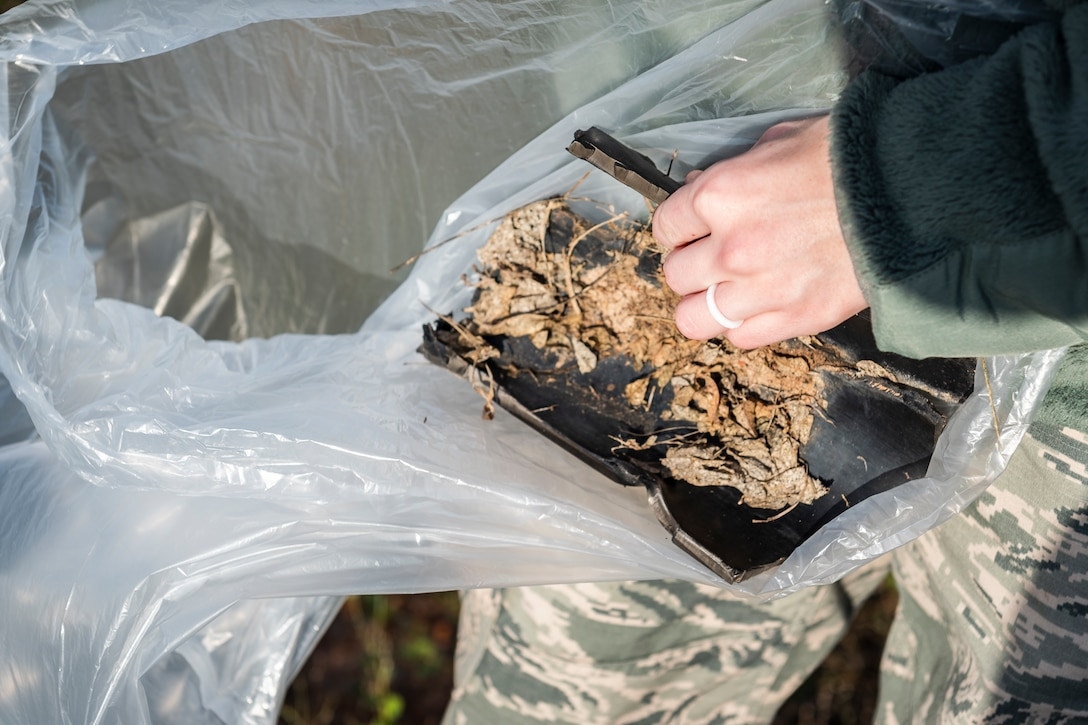 A photo of an Airman placing foreign object debris into a trash bag