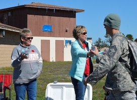 "Members of the Continental U.S. NORAD Region – 1st Air Force (Air Forces Northern) Spouses Club distribute water during a 1.1 – mile ""Ruck March"" Nov. 1 hosted by Combined Enlisted Association. The initiative included more than 50 volunteer marchers with food-filled rucksacks  and collected almost 1,400 pounds of food for a Panama City Beach food bank, Food 4 Kidz. (U.S. Air Force photo by Mary McHale)"