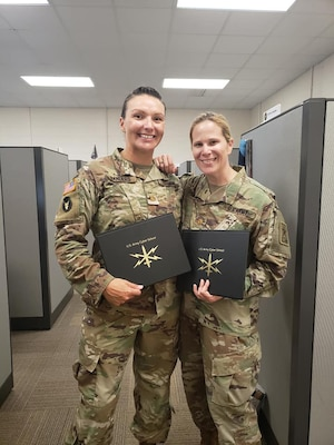 Kentucky National Guard Maj. Dayna Sanders (left) and National Guard Bureau Maj. Monica McGrath (right) receive their certification after completing the Phase 2 Cyber Operations Officer course.