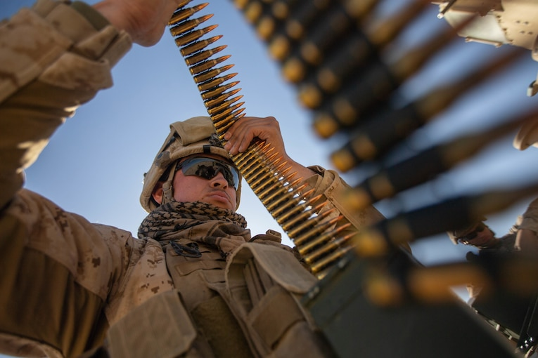 A Marine looks over a roll of bullets.