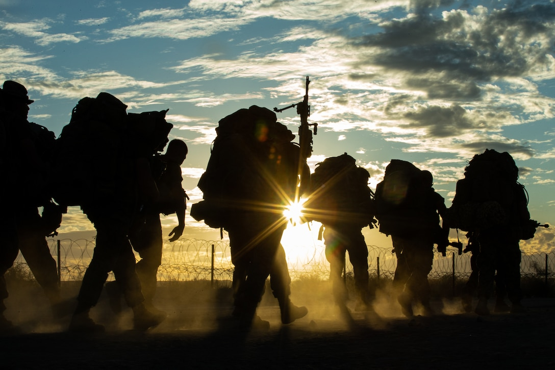 A group of Marines walk together with packs on their backs at twilight.