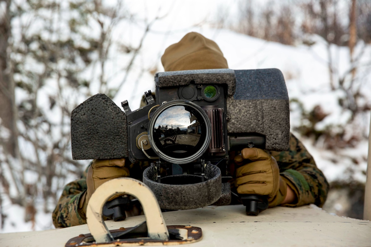 A Marine looks through a large lens in a snowy, wooded area.
