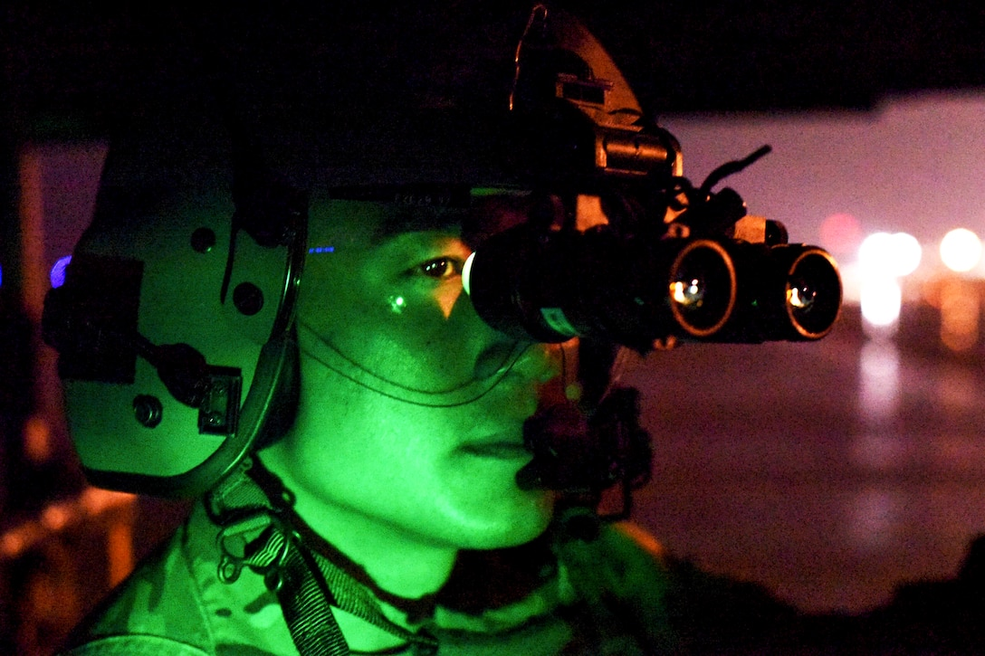 An airman, illuminated in green light, looks through lenses attached to his helmet.