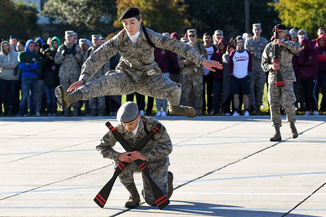 An airman leaps over another airman kneeling on the ground as a crowd watches.