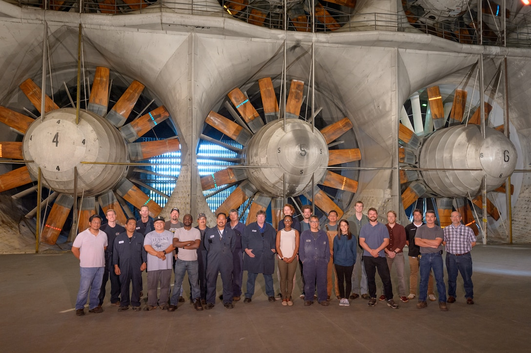 The Arnold Engineering Development Complex National Full-Scale Aerodynamics Complex (NFAC) return-to-service crew document their work on the 40- by 80-foot test section with a photo. In 2017, a collapsed wall panel at NFAC, located at Moffett Field in Mountain View, California, damaged one of the six large fan motors, pictured in the background, which powers the complex wind tunnels. NFAC craftsmen worked alongside engineers to successfully return the 40- by 80-foot test section to service in 2018. (U.S. Air Force photo)