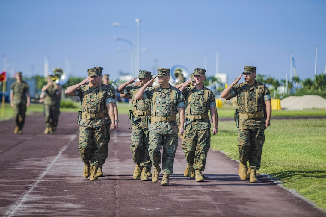 A group of Marines salute.