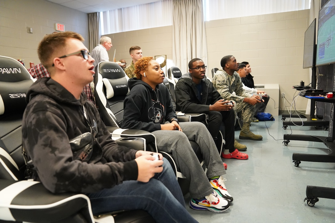 Keesler Airmen play video games during the opening of The Lighthouse inside the Larcher Chapel at Keesler Air Force Base, Mississippi, Nov. 1, 2019. The Lighthouse is a place dedicated to permanent party Airmen complete with gaming stations, massage chairs, a kitchen, and a music room. The idea of the lighthouse stemmed from a meeting Col. Heather Blackwell, 81st Training Wing commander, had with some of Keesler's dorm residents in August. (U.S Air Force photo by Airman 1st Class Spencer Tobler)