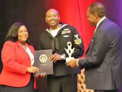 """IMAGE: NORFOLK, Va. (Oct. 29) – Hampton Roads Diversity and Inclusion Consortium (HRDIC) leaders present U.S. Navy Information Systems Technician 1st Class Tyrell Hardison with the Pride Service Award certificate and trophy at a luncheon ceremony. Hardison was one of six awardees recognized at the event for exemplifying diversity and inclusion while serving in the armed forces. """"The Pride Service Award, which we presented to these community leaders, is the first of its kind in our 10 year history,"""" said Mr. Billy McIntyre, HRDIC chairman of the board. """"Today's award recipients have distinguished themselves as leaders and role models in the community and have promoted inclusion in an outstanding manner."""" Left to right: Aleea Slappy Wilson, the Diversity, Equity and Inclusion officer for the city of Norfolk; Hardison; and McIntyre."""