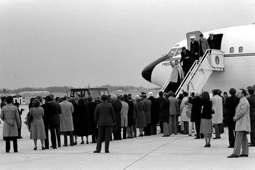 A group of people stand outside an airplane as people deboard.